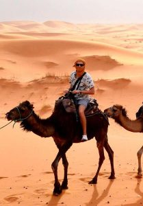 Sitting on a camel in the sahara desert, Morocco