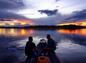 A boat with two men on the Amazon tour in Ecuador during sunset