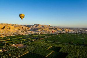 Blick aus dem Heißluftballon auf Luxor mit grünen Wiesen und Wüste