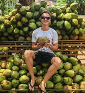 German backpacker sitting on coconuts