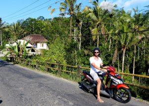 Backpacking Bali mit dem Roller auf einer Straße mit Palmen