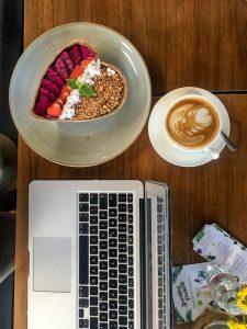Tisch mit Laptop und Müsli Schale und Kaffee