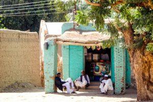 Menschen sitzen vor Gebäude in der Sonne im Sudan