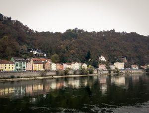 Fluss mit Häusern und Wald im Hintergrund in Passau, Deutschland