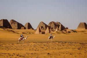 Sudan Rundreise zu den Meroe Pyramiden in der Wüste mit Kamelen davor