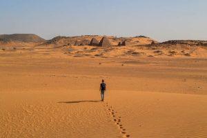 Person läuft durch die Wüste zu den Meroe Pyramiden