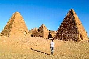 Person läuft in der Wüste vor den Pyramiden von Jebel Barka im Sudan