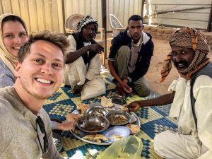 Essen im Sudan mit Einheimischen beim Backpacking