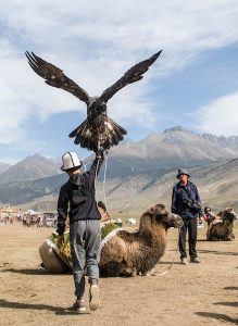 Kleiner Junge mit riesigem Adler in Kirgistan