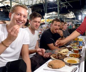 Marokko Urlaub Tipps: Versuche das traditionelle Essen, Personen sitzen an Tisch an Markt in Marrakesch