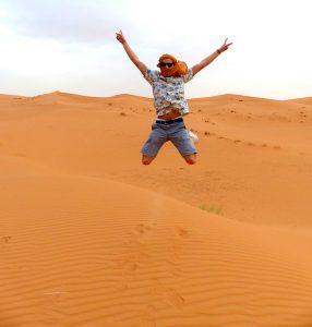 Auf der Wüstentour in die Sahara, Person springt im Sand