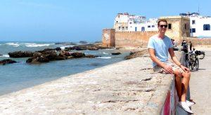 Person sitzt auf Stadtmauer in Essouira, eine Hafenstadt die du besuchen solltest im Marokko Urlaub