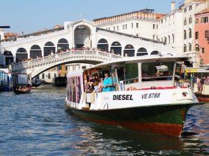 Vaporetto Boot auf Kanal mit Brücke in Venedig im Hintergrund