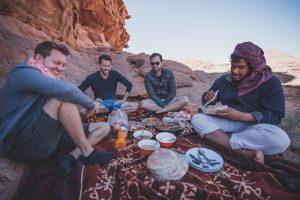 Personen sitzen auf Teppich in Wüste