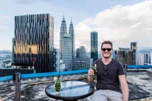 Person an Tisch mit Blick auf Skyline Kuala Lumpur von der Helipad Bar