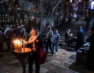 Frau vor Kerze im Marien Grab
