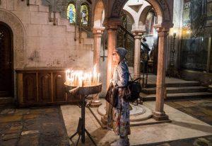 Frau vor Kerzen in Grabeskirche