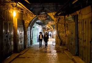 Männer laufen in Altstadt bei Nacht