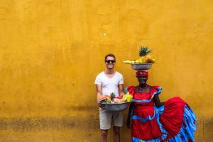 Colorful orange wall with two people in Cartagena while backpacking Colombia
