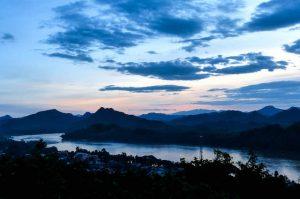 Laos Sehenswürdigkeiten, Ausblick von Hügel auf Landschaft bei Sonnenuntergang