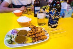 Satay Spies mit Reis und Bier auf Tisch