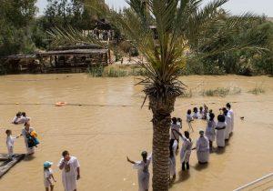 Menschen taufen sich im Jordan Fluss