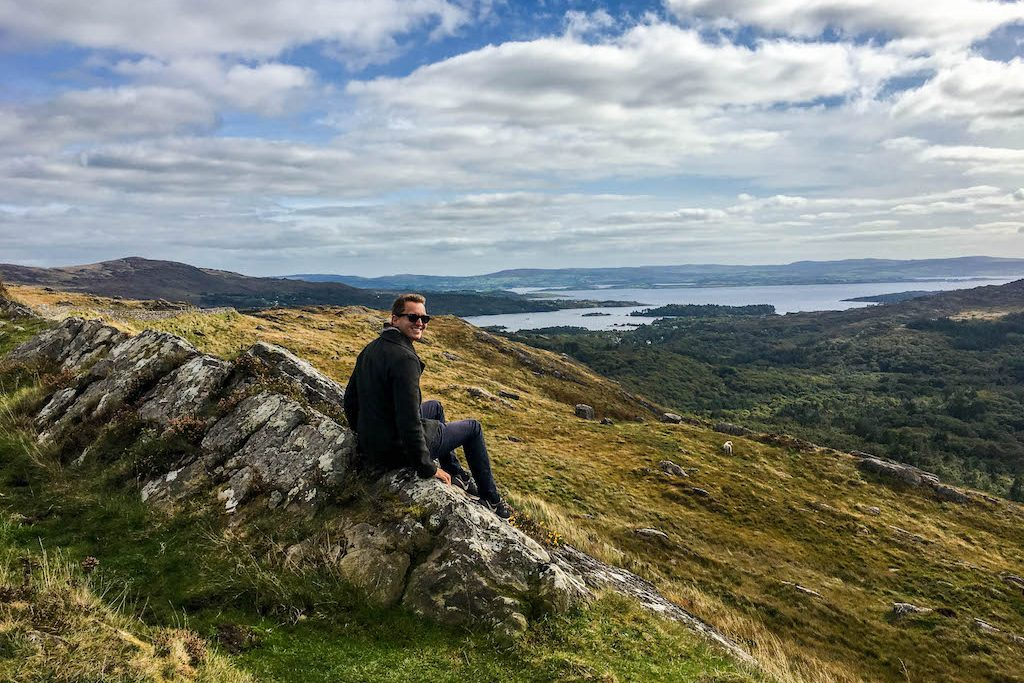Person sitz auf Stein Blick auf Landschaft