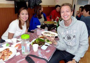 Zwei Personen am Tisch beim Essen auf dem Markt