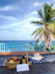 Tisch mit Obst und Rum vor Meer und Palme