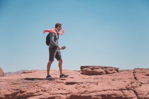 Person mit Kamera läuft auf Felsen