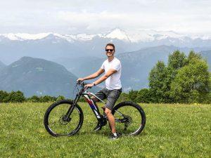 Person auf Fahrrad auf Wiese mit Bergen im Hintergrund