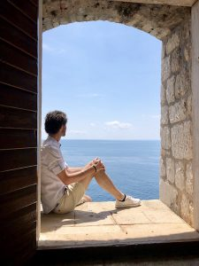 Person sitzt in Fenster mit Blick aufs Meer