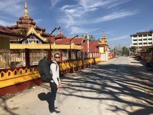 Person mit Rucksack in Myanmar vor einem Tempel