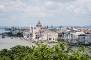 Blick das eine der tollsten Sehenswürdigkeiten in Budapest, das Parlament, von weiter weg mit Baum im Vordergrund