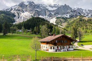 Wiese mit Haus und Berge im Hintergrund