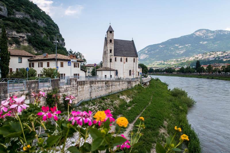 Blick auf Kirche und Blumen im Vordergrund, rechts ist ein Fluss