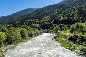 Der große Fluss mit Wald am Rand in Trentino Italien