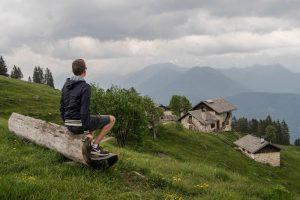 Person sitzt auf bank mit Blick auf Häuser im Tal und Berge im Hintergrund in Trentino