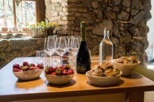 Tisch mit Wein und Schalen mit Obst