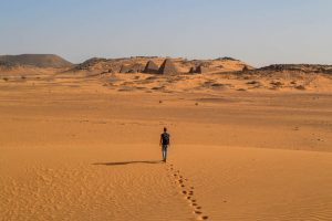 Person läuft in Wüste im Sudan mit viel Sand