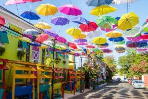 Bunte Straße mit Regenschirmen drüber