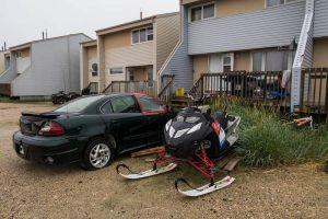 Auto und Schneefahrzeug vor Haus