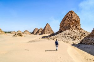 Walking through the desert with pyramids