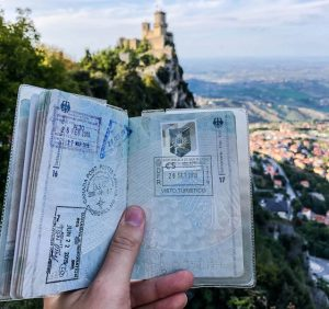 Reisepass mit Stempel vor Berg und Turm