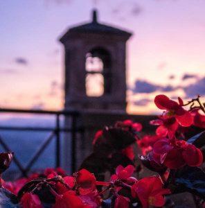 Blumen im Vordergrund, Sonnenuntergang am Himmel und Turm dahinter
