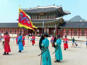 Südkorea Sehenswürdigkeiten in Seoul vor Palast mit Menschen und Fahnen