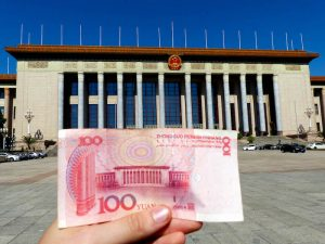 Great Hall of the People with a yuan bill in the front