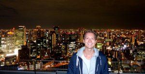 Aussicht vom Umeda Sky Building auf Osaka bei Nacht mit Person davor