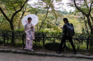 Japanerin und Fotograf vor Bäumen