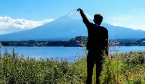 Person streckt Hand und berührt den Fuji Vulkan in Japan
